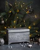 Beautiful concept greeting card of vintage chest over fir-tree branches with sparkling garland background stock image