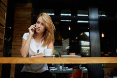 Beautiful concerned female having cell telephone conversation while sitting at the wooden table with sweet dessert Stock Photography