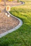Beautiful Concrete Coping Along Lush Green Grass in Yard. Royalty Free Stock Photo