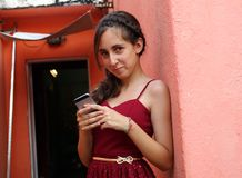 Beautiful confident Argentinian girl using a cell phone, red dress in red painted house. Beautiful confident Argentinian girl using a cell phone, red dress in Royalty Free Stock Photo
