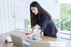 Beautiful Confident asian young business woman working and pointing laptop computer with tablet and document file graph on desk. And White board background in stock photo