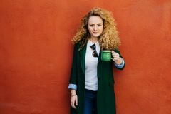Beautiful confident blonde curly woman wearing elegant jacket and jeans holding green mug with tea posing against orange backgroun royalty free stock photos