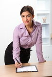 Beautiful confident business woman looks up from w Royalty Free Stock Photo