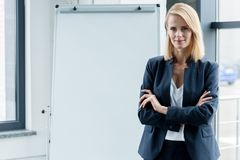 beautiful confident businesswoman standing with crossed arms and smiling at camera stock photo
