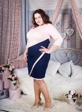 Beautiful confident buxom woman plus size. Beautiful confident buxom woman in a pink dress stay in full-length at the room royalty free stock image