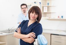 Beautiful and confident dentist woman and male assistant Royalty Free Stock Photos