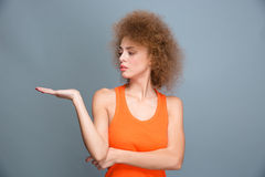 Beautiful confident female holding copyspace on the palm Stock Photos