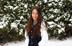 Beautiful confident green eyes teenager walking under snow while snowing royalty free stock photography