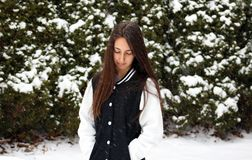 Beautiful confident green eyes teenager walking under snow while snowing stock image
