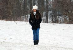 Beautiful confident green eyes teenager walking under snow while snowing stock photo