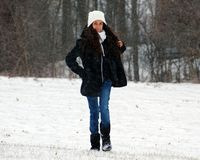 Beautiful confident green eyes teenager walking under snow while snowing stock photos