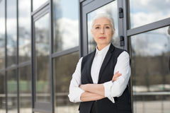 Beautiful confident senior businesswoman standing with crossed arms and looking at camera Royalty Free Stock Image