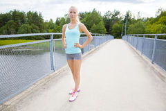 Beautiful and confident young female runner stands at bridge Royalty Free Stock Photo