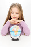 Beautiful confident young girl is watching at the world globe. And dreaming Stock Images