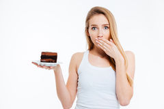 Beautiful confused woman on diet holding piece of chocolate cake Stock Images