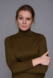 Beautiful confused woman with a raised eyebrow. Isolated on grey Stock Photography