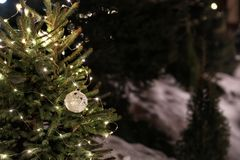 Beautiful conifer tree with glowing Christmas lights and ball outdoors, space for text stock photo