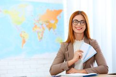 Beautiful consultant holding tickets in travel agency. Space for text royalty free stock photos