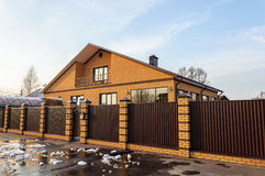 Beautiful contemporary brick house behind a metal fence Stock Photo