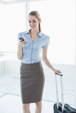 Beautiful content businesswoman using her smartphone standing in her office Royalty Free Stock Photography