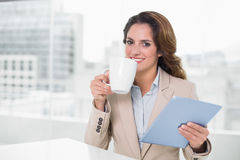 Beautiful content businesswoman using tablet drinking coffee Royalty Free Stock Image