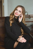 Beautiful content smiling young female talking on mobile phone Stock Photography