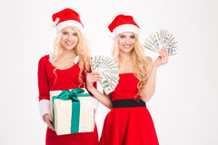 Beautiful content young sisters twins have got money and gift Royalty Free Stock Images