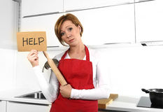 Beautiful cook woman in angry upset and frustrated face expression wearing red apron asking for help holding rolling pin Stock Image