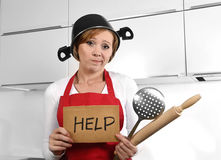 Beautiful cook woman confused and frustrated face expression wearing red apron asking for help holding rolling pin. Young cook woman confused and frustrated face Royalty Free Stock Photography