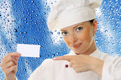 Beautiful cook woman holding blank card Royalty Free Stock Image