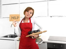 Beautiful cook woman in sad and frustrated face expression wearing red apron asking for help holding rolling pin Stock Photography