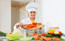 Beautiful cook woman in uniform prepares veggie lunch Stock Photos