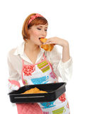 Beautiful cooking woman eating croissant Stock Images