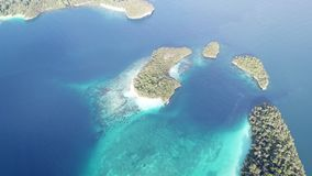 Aerial View of Tropical Islands and Reefs in Raja Ampat. Beautiful coral reefs fringe the many tropical islands within Raja Ampat, Indonesia. This remote region stock footage