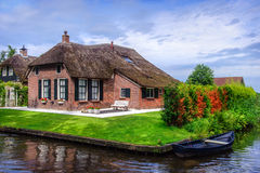 Beautiful cottage surrounded by canal in Giethoorn. Giethoorn, also known as the Venice of Holland or the Venice of the North, is a beautiful village in the Royalty Free Stock Photo