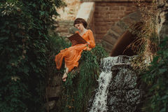 The beautiful countess in a long orange dress. Sits near a source of water and reading a book, elf, Princess in vintage dress, the queen of the forest Stock Images