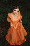The beautiful countess in a long orange dress. Is walking in a green forest full of branches, elf, Princess in vintage dress, the queen of the forest stock images