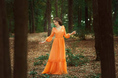 The beautiful countess in a long orange dress. Is walking in a green forest full of branches, elf, Princess in vintage dress, the queen of the forest royalty free stock image