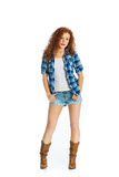 Beautiful country girl. An attractive young woman with red hair and freckles wearing short denim shorts and cowboy boots Royalty Free Stock Images