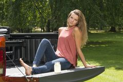 Beautiful country girl on back of pick-up truck. Beautiful young country girl poses with jar of lemonade in back of pickup truck on farm wearing blue jeans Stock Photos