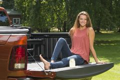 Beautiful country girl on back of pick-up truck. Beautiful young country girl poses with jar of lemonade in back of pickup truck on farm wearing blue jeans Royalty Free Stock Images