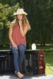 Beautiful country girl on back of pick-up truck. Beautiful young country girl poses with jar of lemonade in back of pickup truck on farm wearing blue jeans Royalty Free Stock Photos
