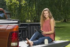 Beautiful country girl on back of pick-up truck. Beautiful young country girl poses with jar of lemonade in back of pickup truck on farm wearing blue jeans and Stock Photography