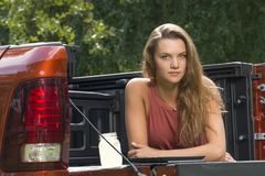 Beautiful country girl on back of pick-up truck. Beautiful young country girl poses with jar of lemonade in back of pickup truck on farm wearing blue jeans and Stock Photo