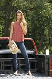 Beautiful country girl on back of pick-up truck. Beautiful young country girl standing int the bed of a pickup truck on farm wearing blue jeans Royalty Free Stock Image