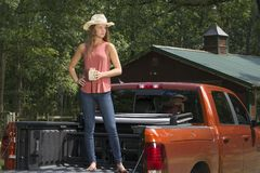 Beautiful country girl on back of pick-up truck. Beautiful young country girl standing int the bed of a pickup truck on farm wearing blue jeans Stock Image