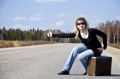 Beautiful country girl hitchhiking on the road royalty free stock images