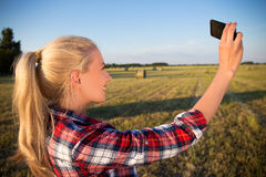 Beautiful country girl making selfie photo on smartphone in fiel Royalty Free Stock Images