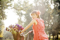 Beautiful country girl riding a bike through nature, enjoying sunny day. Stock Images