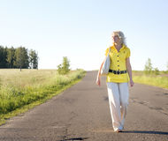 Beautiful country girl walking on the road stock photography